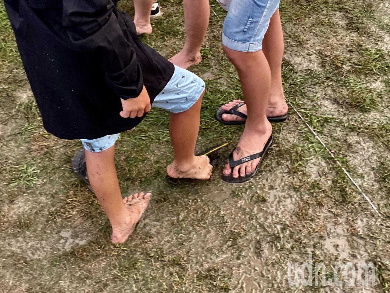 國慶焰火會場因大雨積水滿是泥濘,不少民眾索性脫下鞋襪,赤腳踩著泥巴,站在舞台前欣...