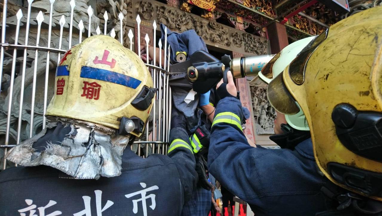 工人為了掛紅布條卻意外從梯上摔下,當場遭鐵柵刺穿左手臂,出動消防人員救援。記者巫...