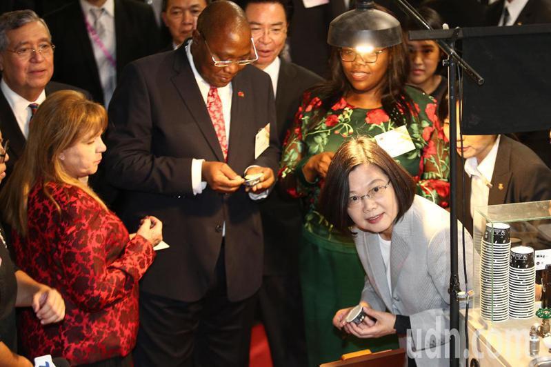 蔡英文總統(右下)晚上出席「中華民國108年國慶酒會」,吃包種茶冰淇淋時,探頭回應拍照要求。記者蘇健忠/攝影