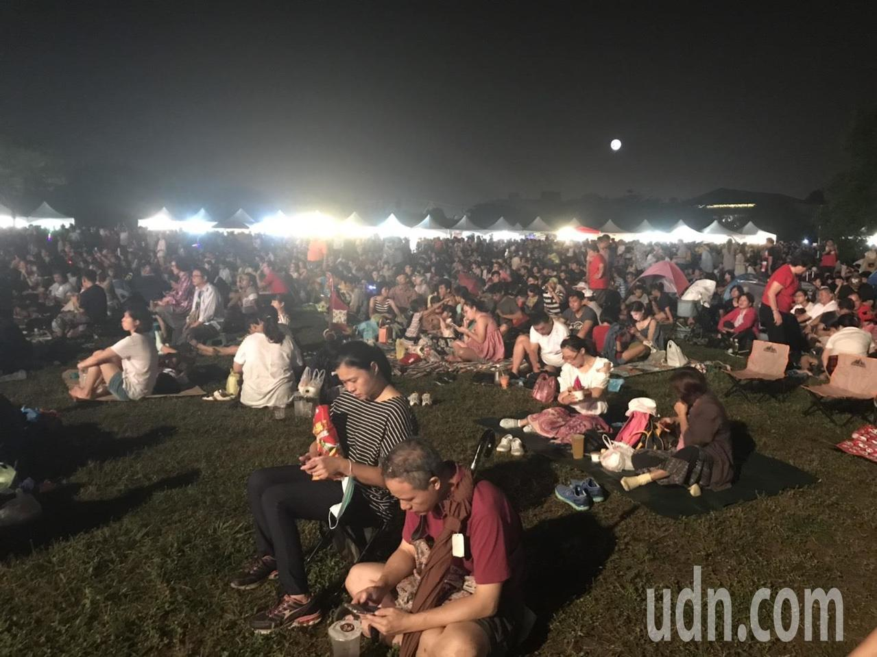 現場聚集數萬觀看焰火人潮,不少人直接在草地上坐下,邊聽音樂邊等待國慶焰火登場。記...