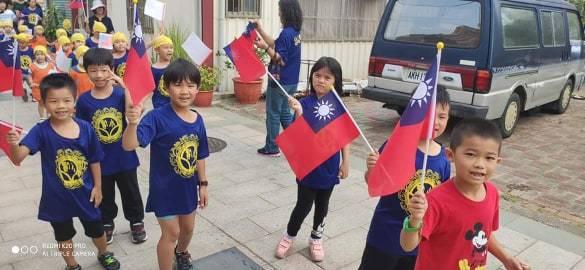金寧鄉垵湖國小學童也在老師帶領下,揮舞著國旗繞行村莊,用不同的方式來慶祝中華民國...