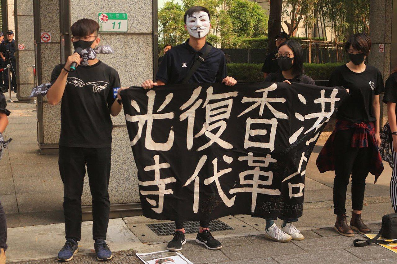 來自東吳、政大等多校的在台港生及聲援者,12日穿著黑衣到位於台北市信義區的香港經...