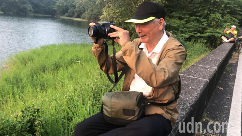 80歲老翁盧正雄,迷上蘭潭水庫夕照美景,每天拿相機拍照並錄影蘭潭落日美景,上傳臉書及YouTube與親友分享。記者魯永明/攝影