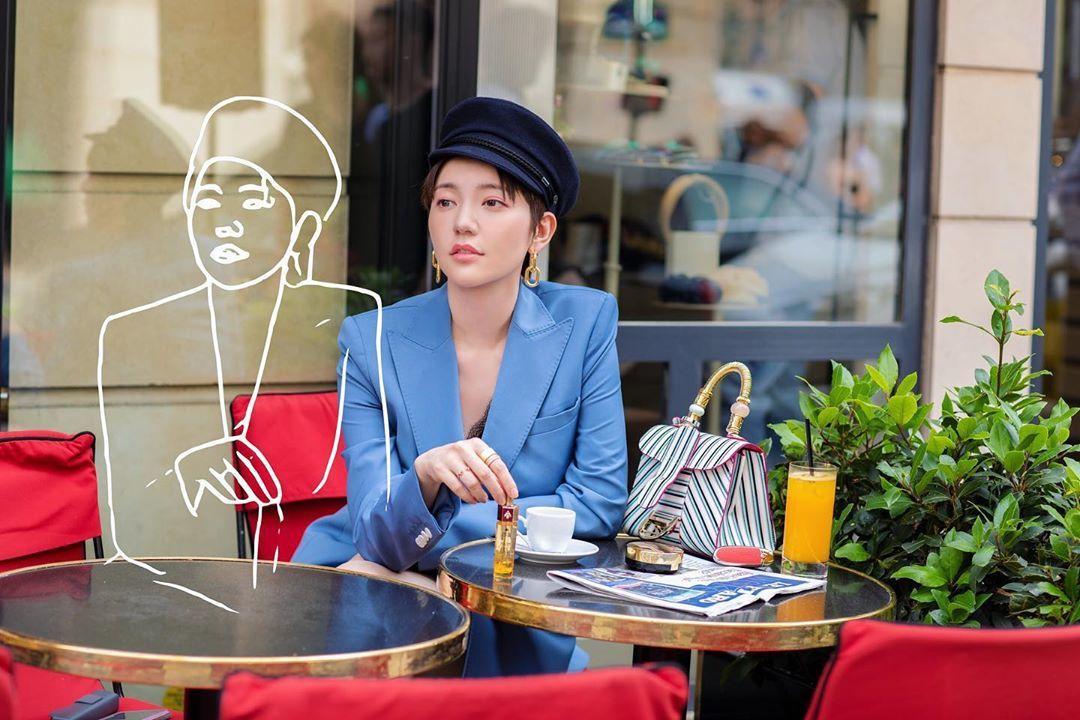 郭雪芙在巴黎咖啡館浪漫街拍,桌上是DELVAUX的Brillant系列條紋包款。...