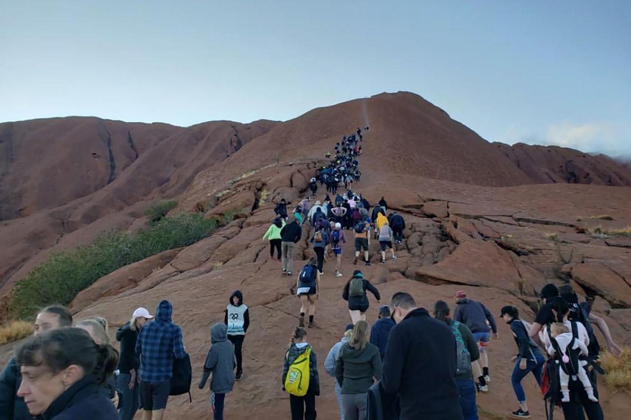 澳洲遊客在烏魯魯禁爬令生效前搶著攀登,形成一條長長人龍,蔚為奇觀。法新社