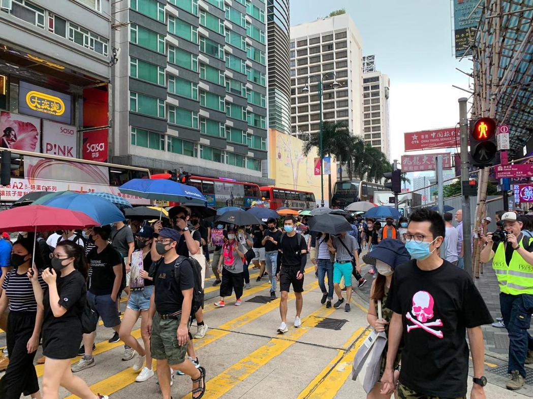 戴口罩的示威者占用彌敦道北行線道路,影響交通。圖:取自星島日報網站