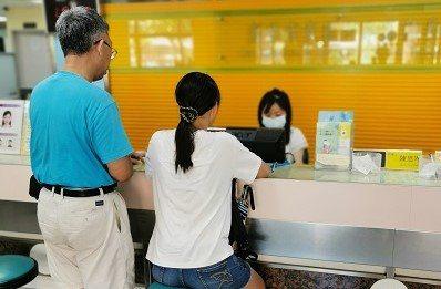 年滿14歲的國中女生(右)初領身分證,在戶政人員的協助下,母親欄位不再空白。圖/...