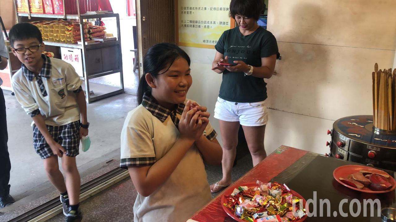 嘉義市精忠國小5年級學生凃睿恆(左)和何芝云(右)為廟方製作ORcode解籤。記...