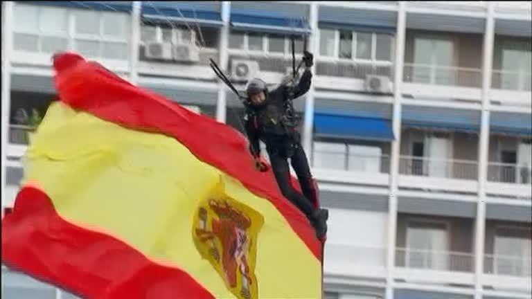 西班牙12日國慶閱兵上,傘兵攜帶國旗從天而降,向前來觀禮的國王致敬。路透