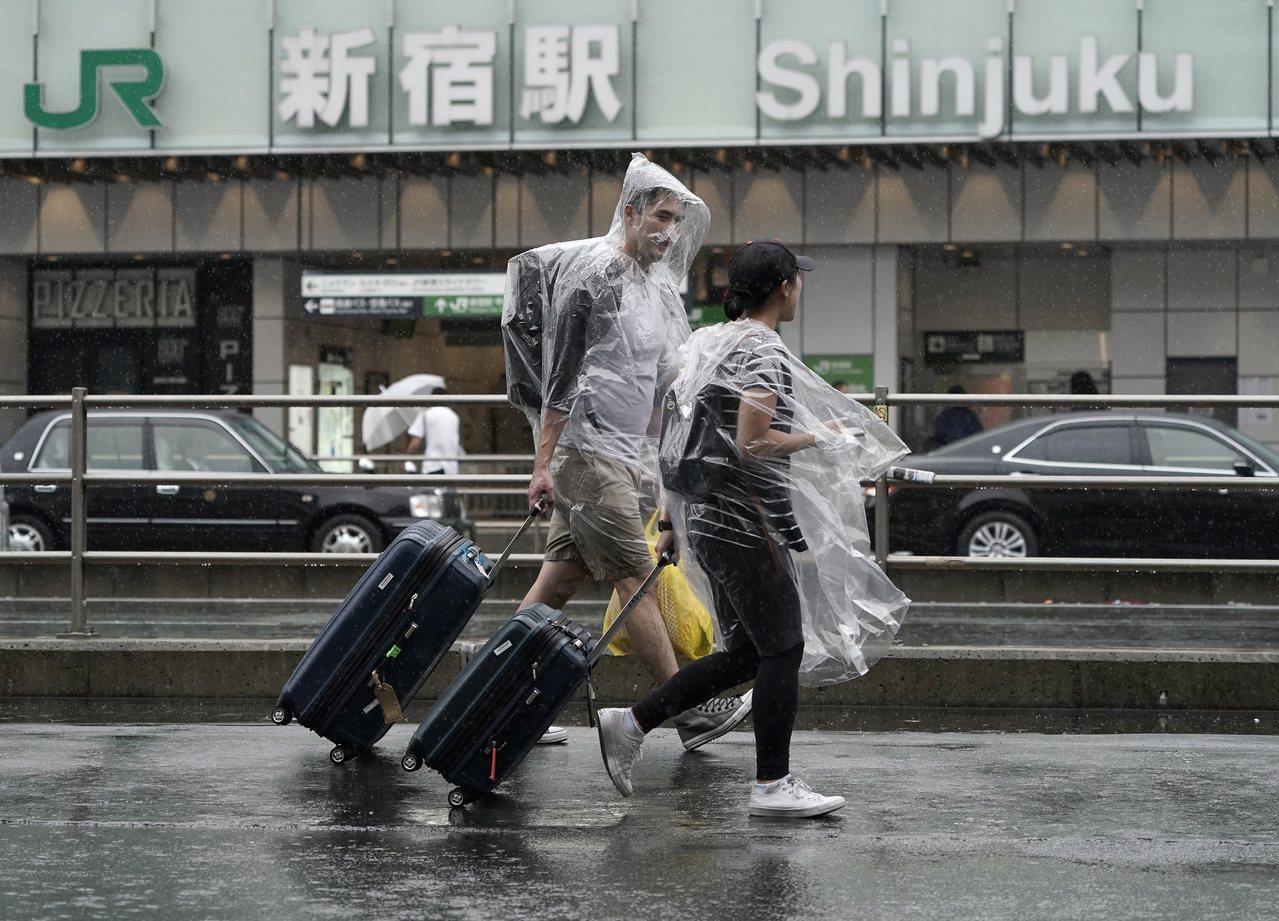 圖為兩名走在東京街頭、穿著塑膠雨衣趕路的外籍遊客。歐新社
