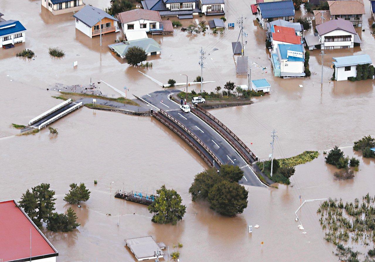 哈吉貝颱風造成日本中部長野市堤防潰決,長野市十三日泡在泥水中。 (美聯社)