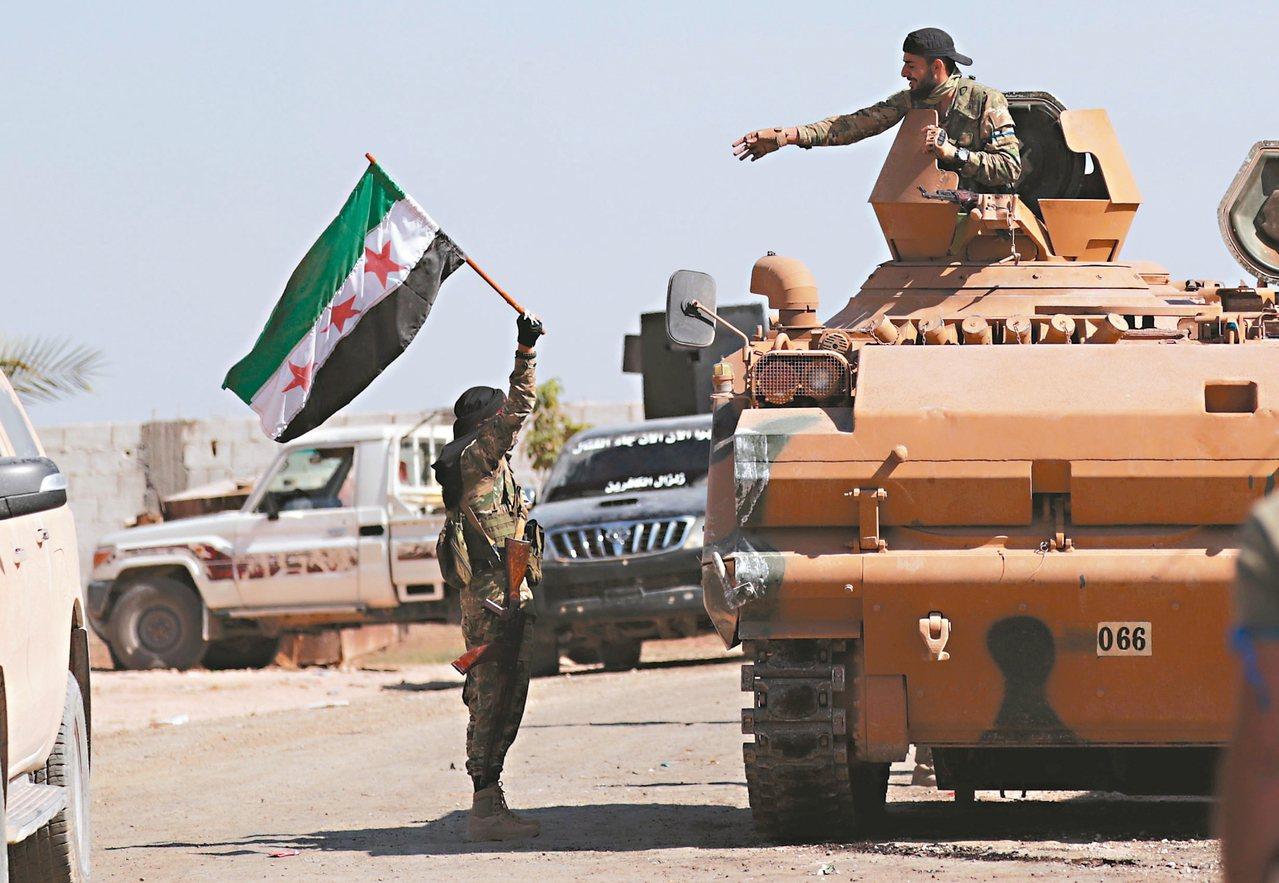 土耳其支持的敘利亞民兵十二日在敘利亞邊境城鎮泰阿巴揮舞他們的旗幟。 (路透)