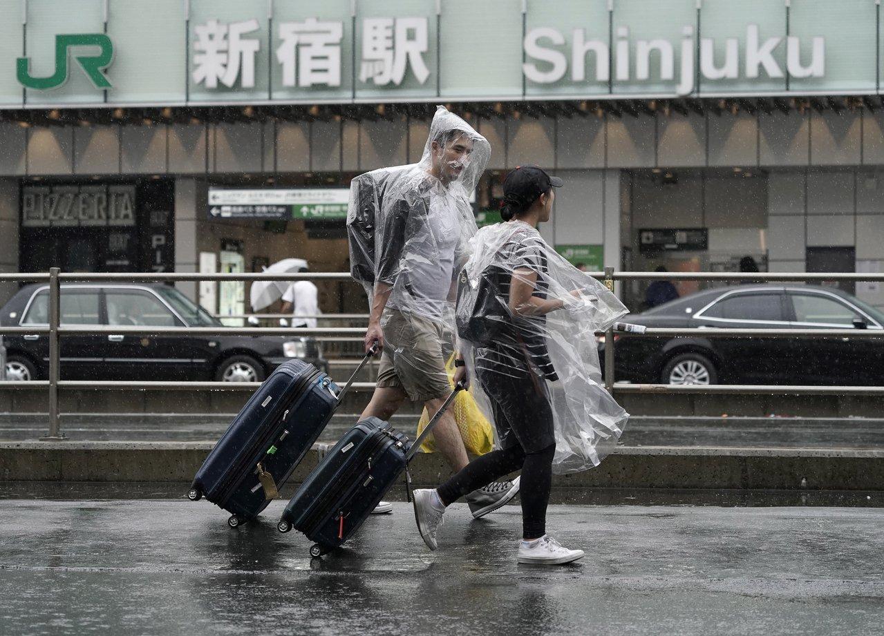 兩名走在東京街頭、穿著塑膠雨衣趕路的外籍遊客。(歐新社)