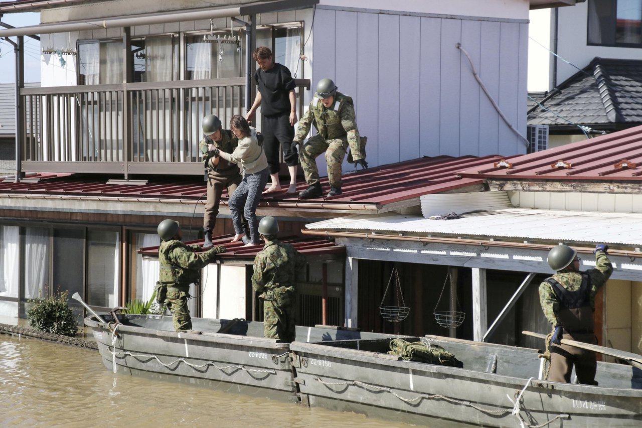 哈吉貝颱風造成日本多處水災,自衛隊十三日在宮城縣角田市救出受困民眾。(路透)