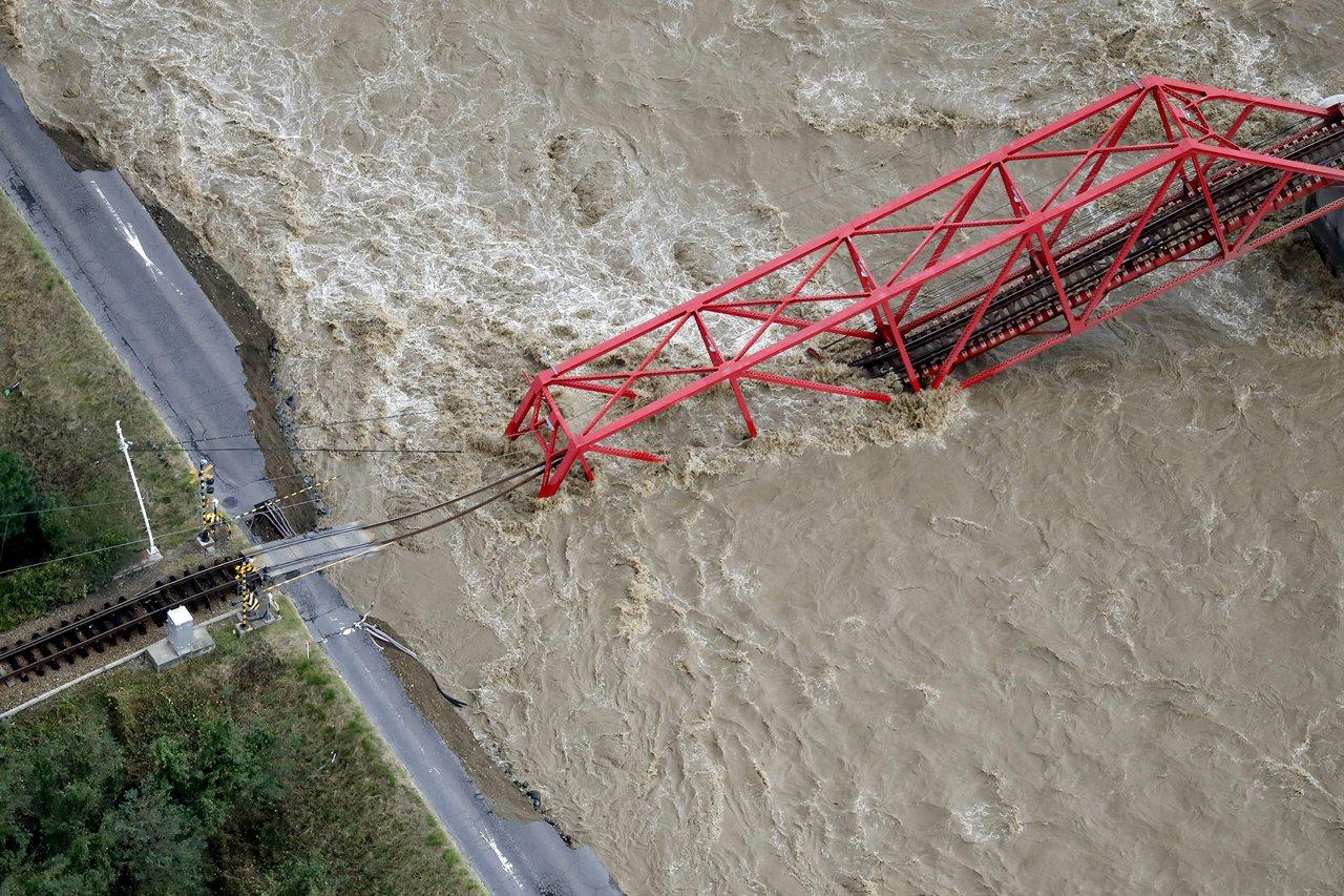 十三日的照片顯示,哈吉貝颱風帶來暴雨,沖垮日本長野縣上田市一座鐵路橋。(美聯社)