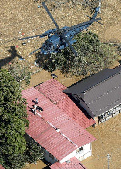 哈吉貝颱風帶來大雨,居民十三日在屋頂上等待直升機救援。(美聯社)