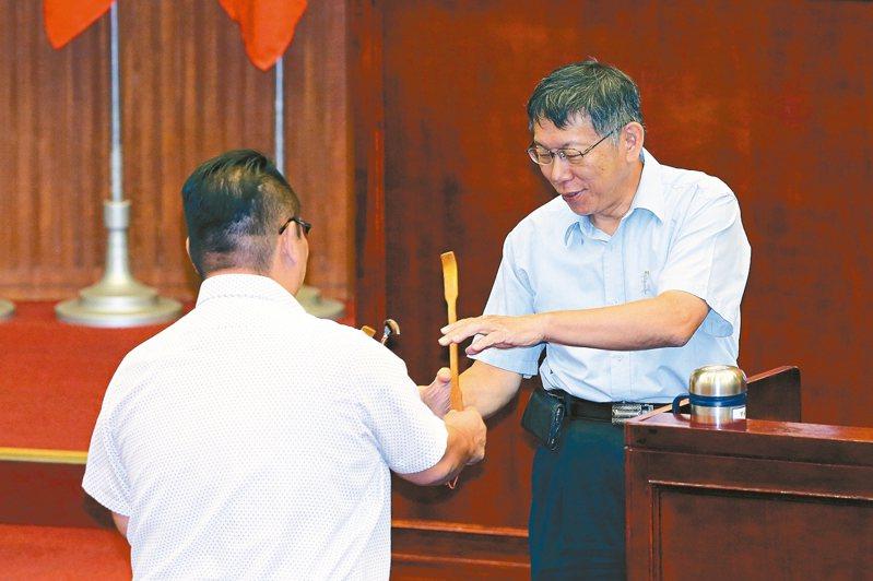台北市議會上午進行質詢時,議員陳重文(左)質疑市府內部有「抓耙子」,特別送上抓癢用的「抓耙子」給市長柯文哲(右)。 記者許正宏/攝影