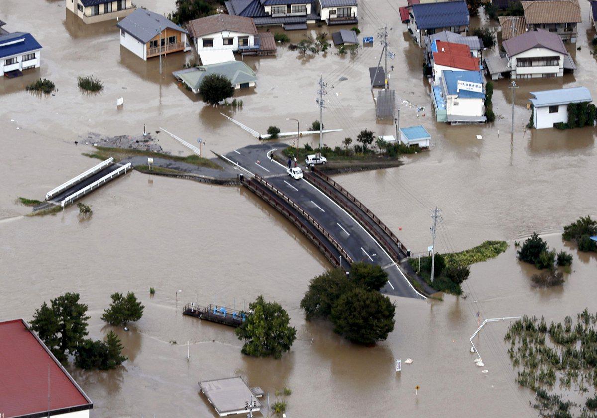 長野千曲河大堤破裂後,城市被淹沒在泥濘的水域中,汽車被困在道路上。美聯社