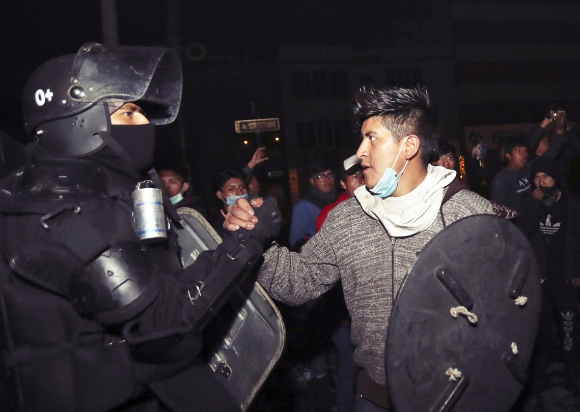 政府與示威代表談判成功後,在基多街頭連打12天的示威者,與鎮暴警察握手和解。 圖...
