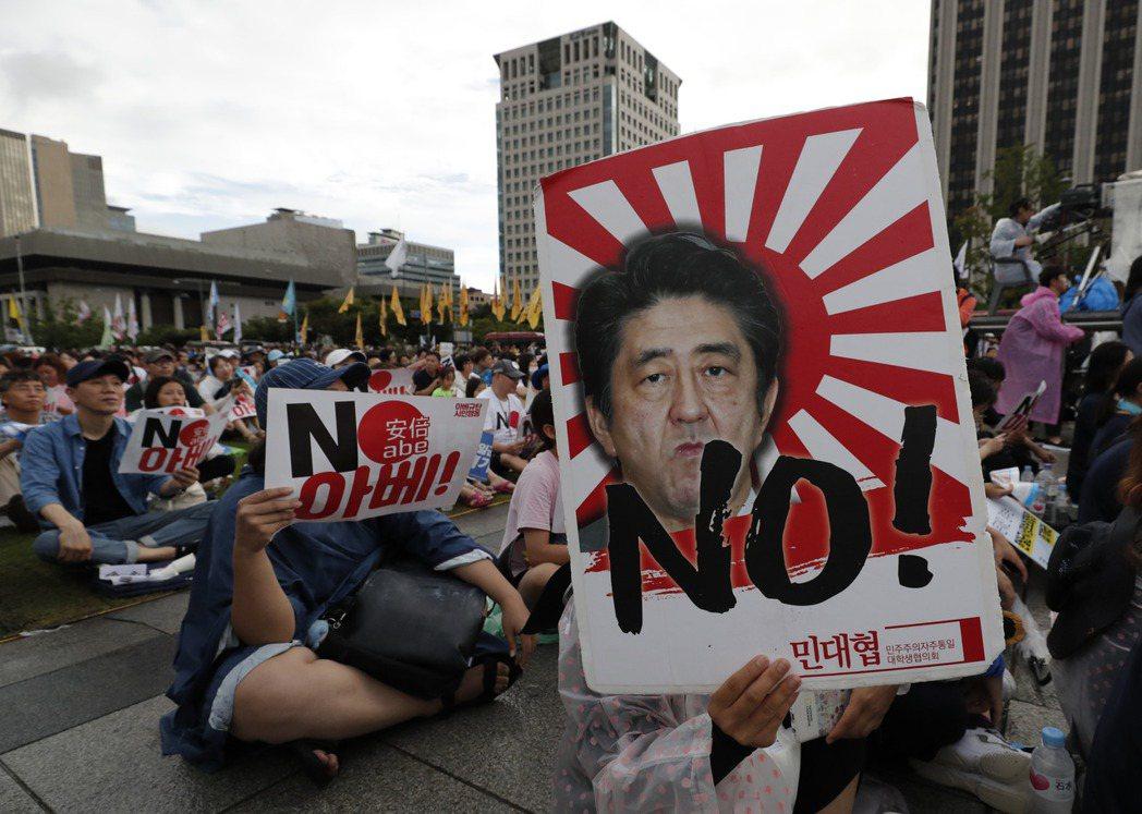 一位南韓示威者在抗議日韓貿易戰時,舉起反日圖板。  美聯社