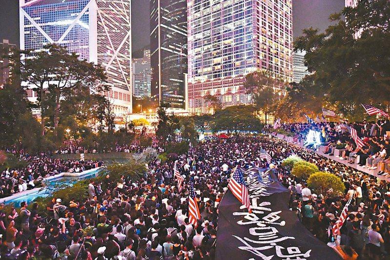 香港反送中示威者昨晚在中環遮打花園,舉行聲援美國國會審議「香港人權與民主法案」集會,現場有人揮舞著美國國旗。據大會公布,參與集會人數為13萬人。 (法新社)