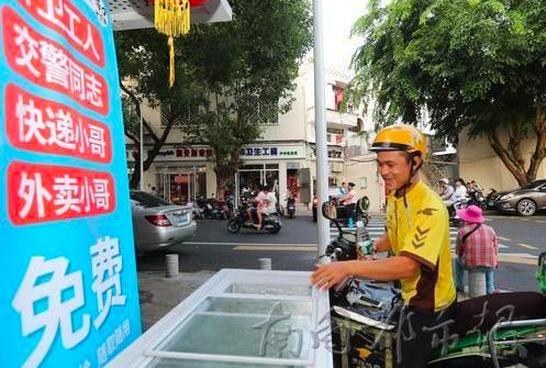 一名外賣小哥從愛心冰箱中取水喝。 (南國都市報)