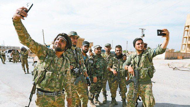 土耳其軍隊攻下敘利亞邊界城市泰勒艾卜耶德後,土耳其支持的敘利亞民兵14日在城內自...