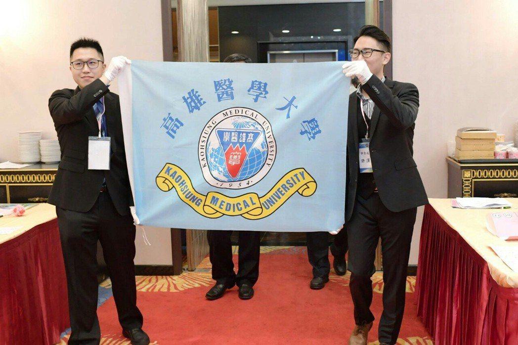 高醫醫學系20屆已故同學許吉成的兒子許漢強(右)代替父親參加同學會,高舉校旗高唱...
