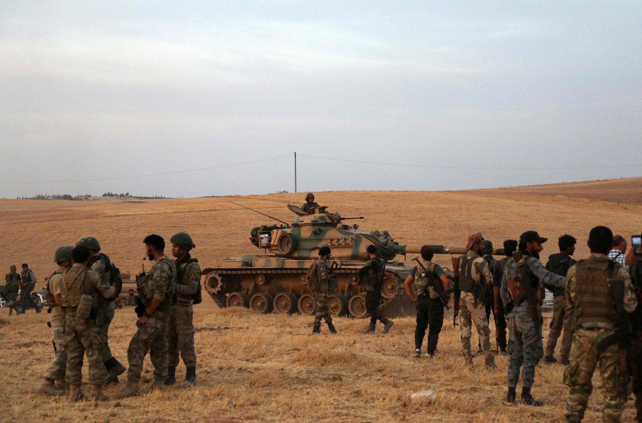 土耳其部隊及土國支持的敘利亞戰士14日聚集在敘土邊界附近的曼比季市市郊。法新社