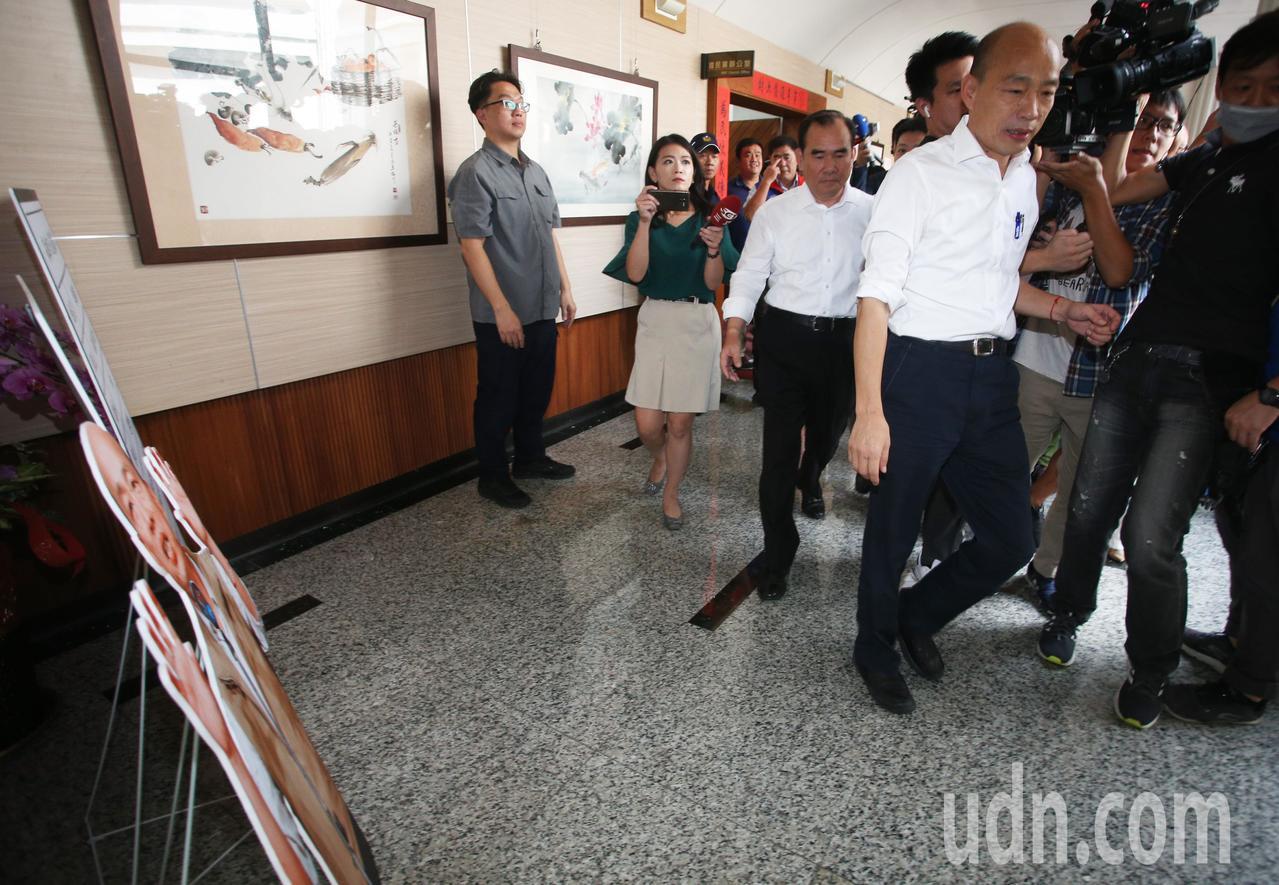 高雄市長、國民黨總統參選人韓國瑜(前)從高雄市議會民進黨團門口經過,未看黨團門口...