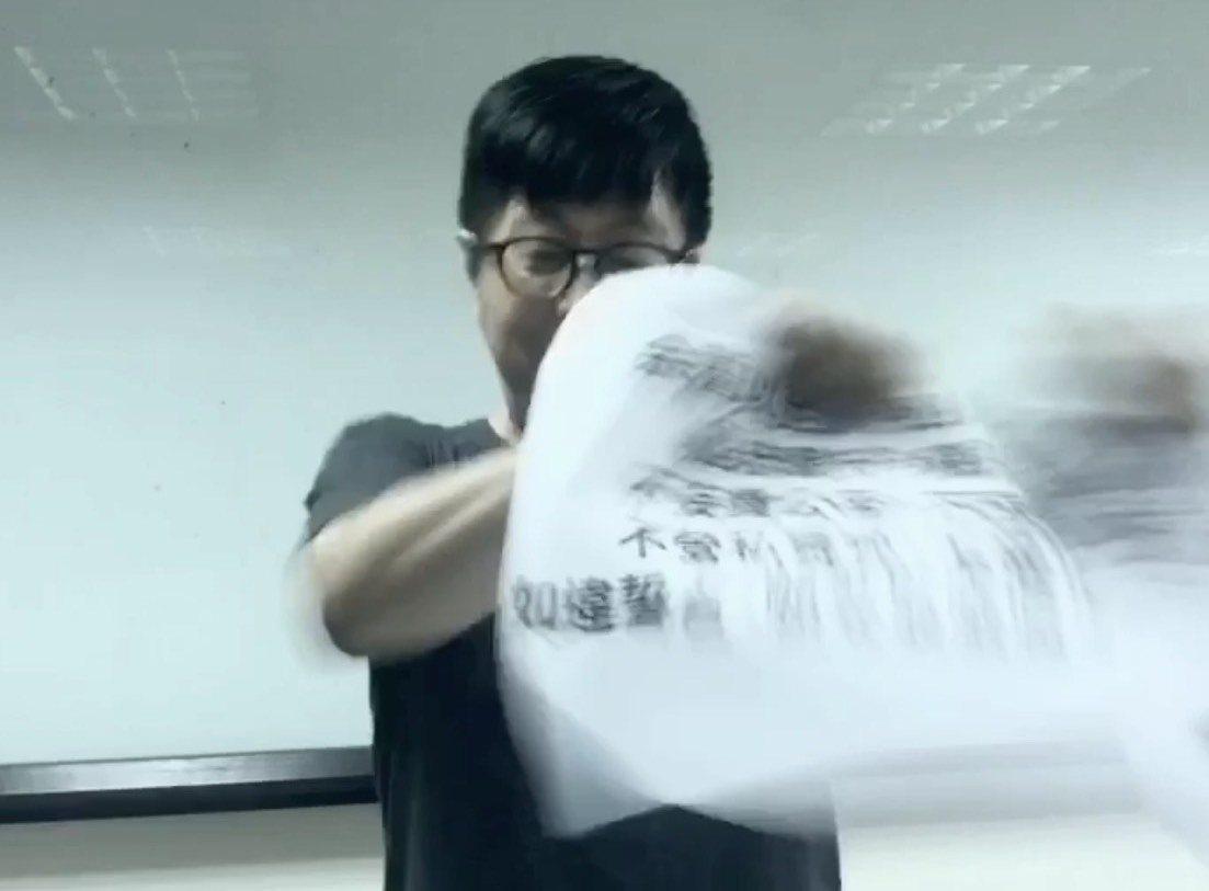 社群Wecare高雄發起人尹立,作勢撕毀韓國瑜十個月前的宣誓就職誓詞。圖/摘自社...