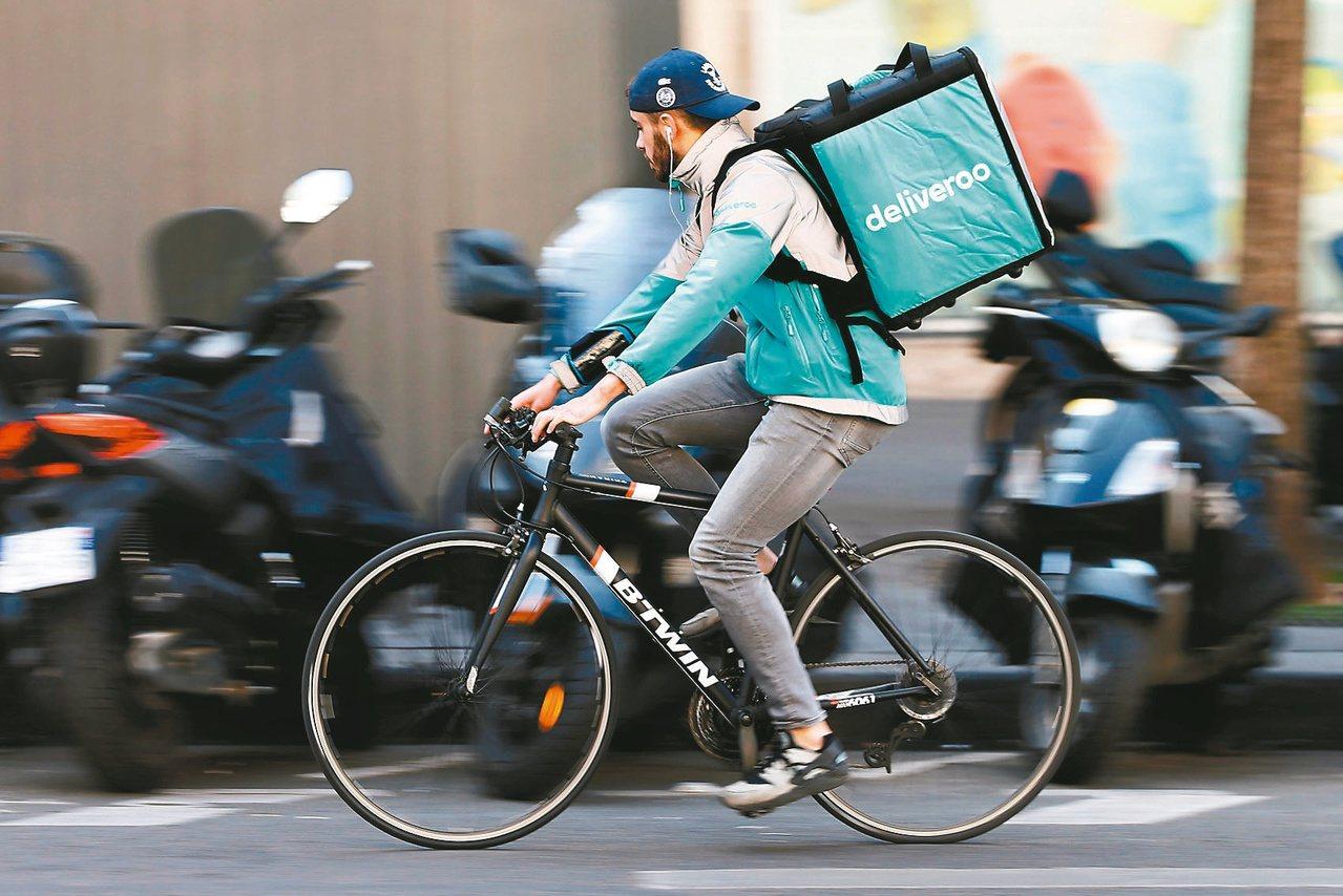 一名男子騎著單車在巴黎街頭幫Deliveroo餐點外送公司宅配外賣。路透