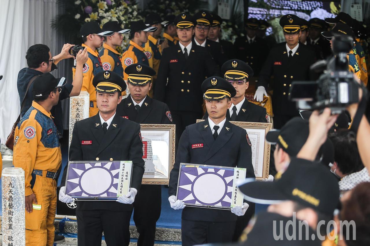 殉職消防員謝志雄、張哲嘉同袍捧著覆棺旗步出會場。記者黃仲裕/攝影