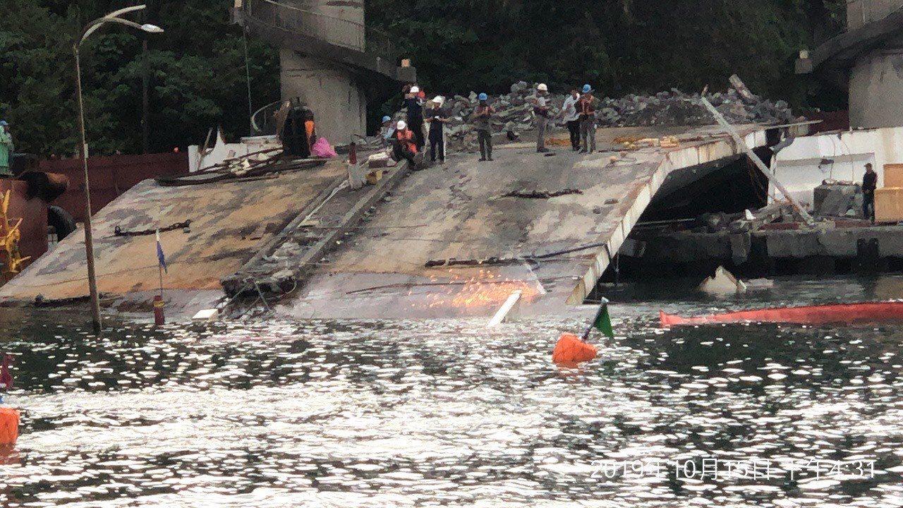 工程人員以「鑽石鏈鋸」切下跨港斷橋橋面的第一刀,現場火花四射。圖/台灣港務公司提...
