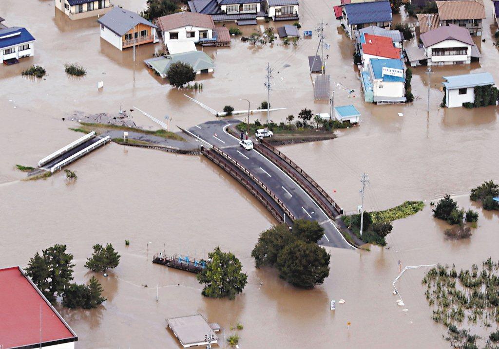 哈吉貝颱風造成日本中部長野市堤防潰決,長野市十三日泡在泥水中。 美聯社