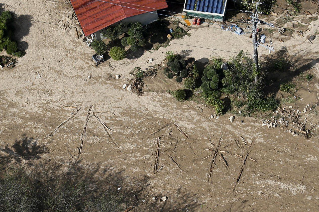 宮城縣丸森町筆甫區一處民居前,有人用倒木或漂流木排成「水、食物」兩組大字,被傳媒...