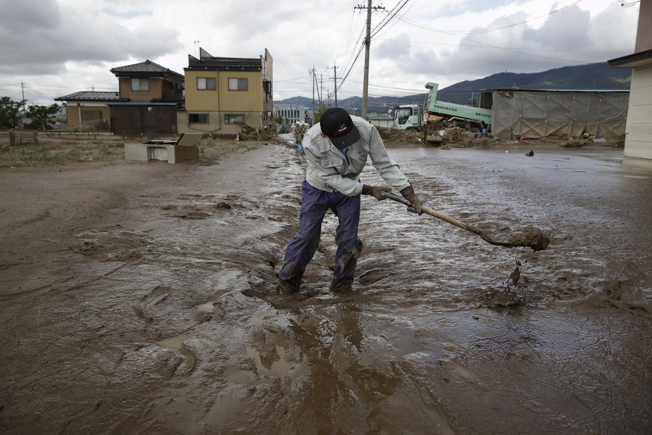 颱風哈吉貝吹襲過後的重災區長野縣15日滿目瘡痍,一名男子清理家園拿鏟子鏟爛泥。 ...