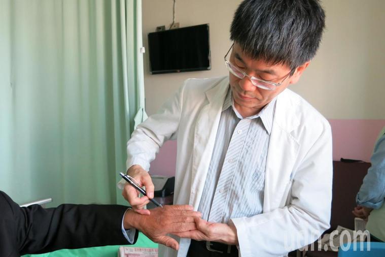 呂男是名豬販,每天要處理豬腳,受傷的雙手常泡在豬的血水中引發感染。記者余采瀅/攝...