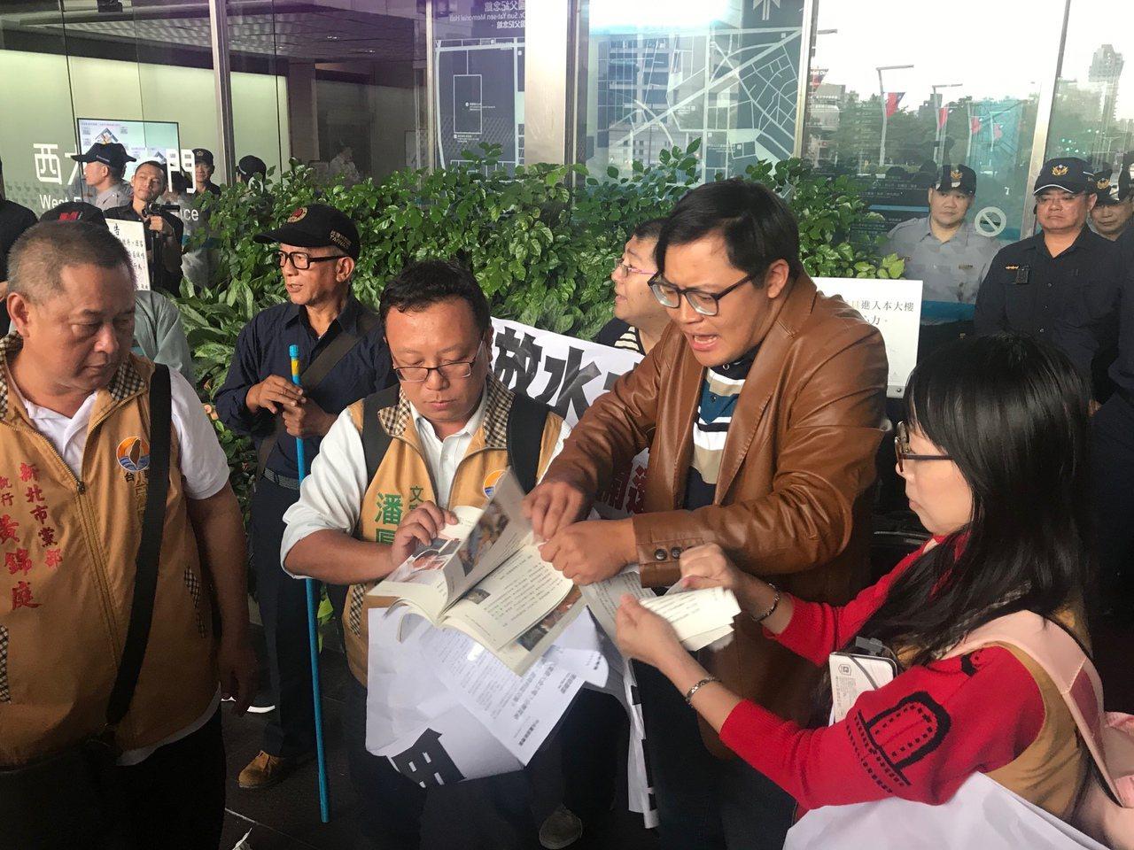 台聯黨成員下午在台北市政府前質疑市府放水讓大巨蛋都審過關,把市長柯文哲寫的書「改...