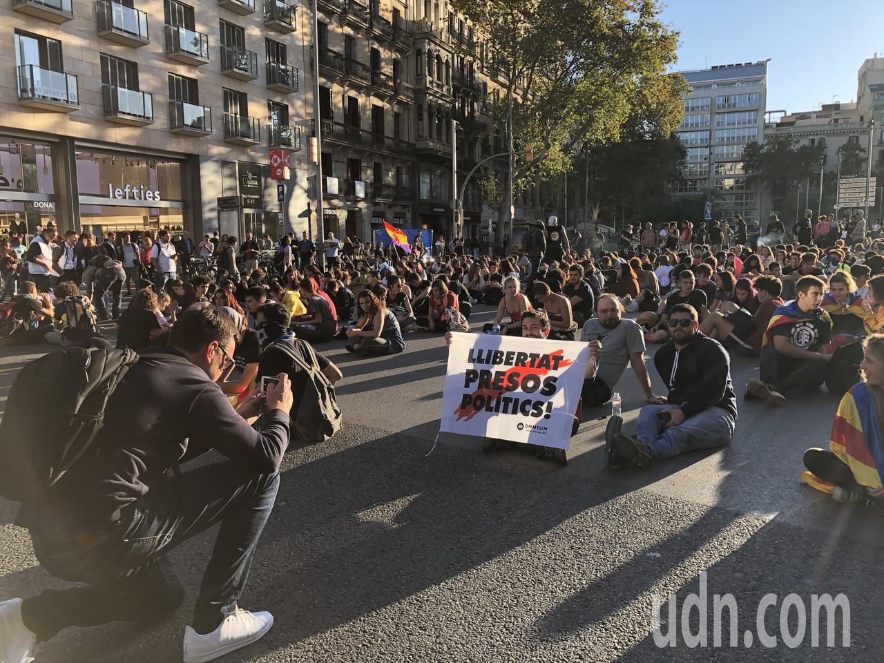 巴塞隆納民眾近日下午5時都到加泰隆尼亞廣場等地靜坐示威,手持海報。記者何定照/攝...