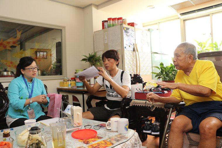 社會局而少科長劉倩如(左)將資料送給曾大原(右)確認認養的對象。圖/新北社會局提...