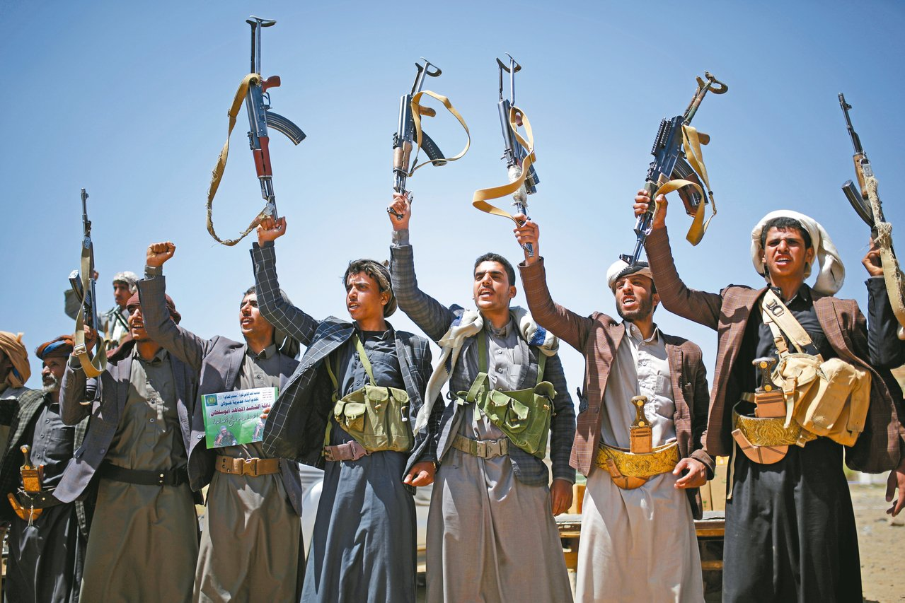 葉門叛軍胡塞組織成員在首都沙那高舉武器,表明忠於組織。 (美聯社)