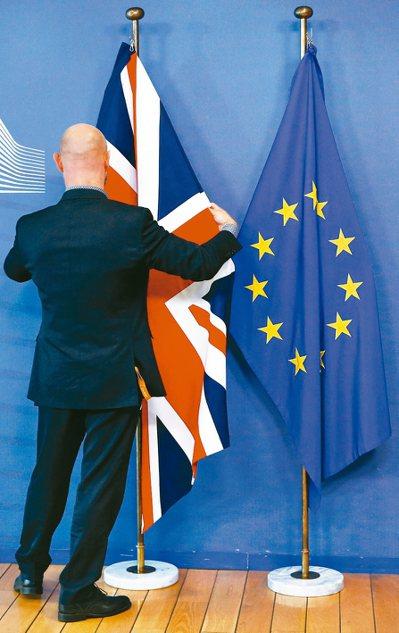 歐盟執委會主席容克與英國首相強生十七日舉行聯合記者會前,歐盟工作人員調整英國國旗...