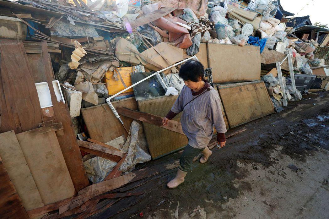 福島縣伊達市梁川町在這次風災嚴重淹水,洪水退去後垃圾雜物堆積如山。(路透)