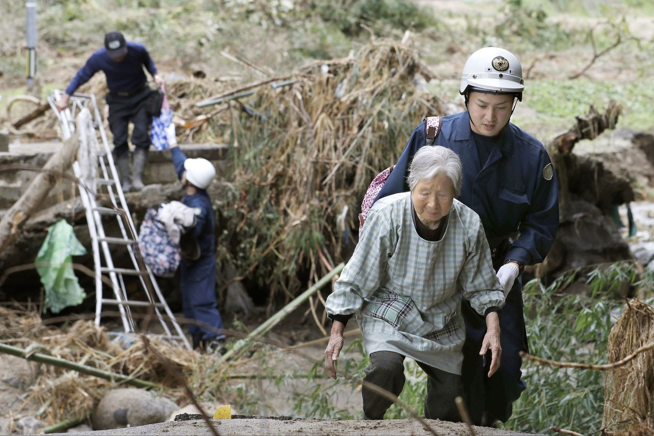 救援人員在福島縣郡山市協助當地老人前往避難所。(美聯社)