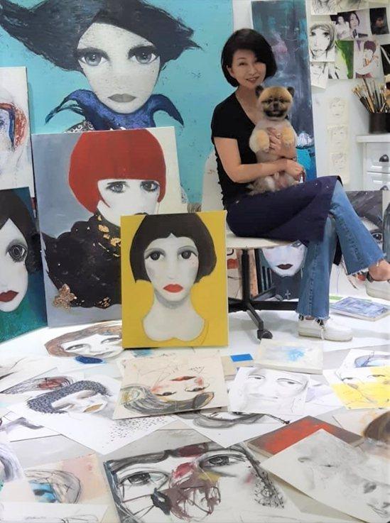 楊林的工作室裡,約有60多幅畫同時進行,圖中的她抱著愛犬「以勒」。(楊林提供)