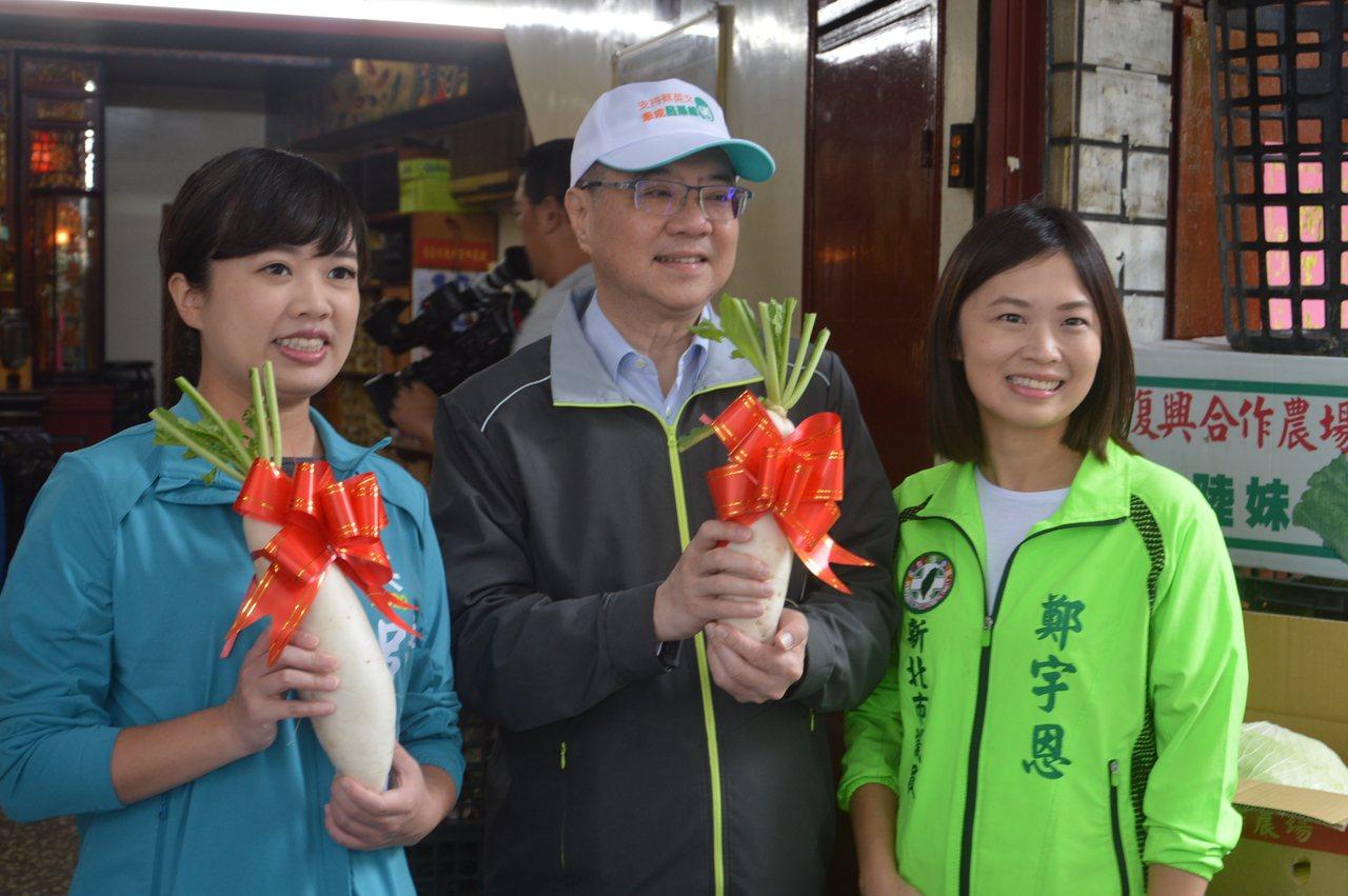 民進黨主席卓榮泰(中)、新北市議員鄭宇恩(右)陪呂孫綾(左)在淡水拜票,支持者送...