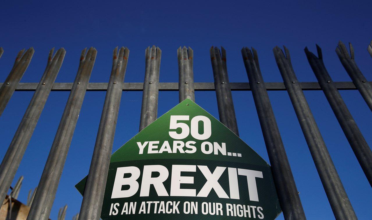 英國北愛爾蘭靠近愛爾蘭的邊界圍籬上,16日掛著反脫歐標語「50年了…英國脫歐會侵...