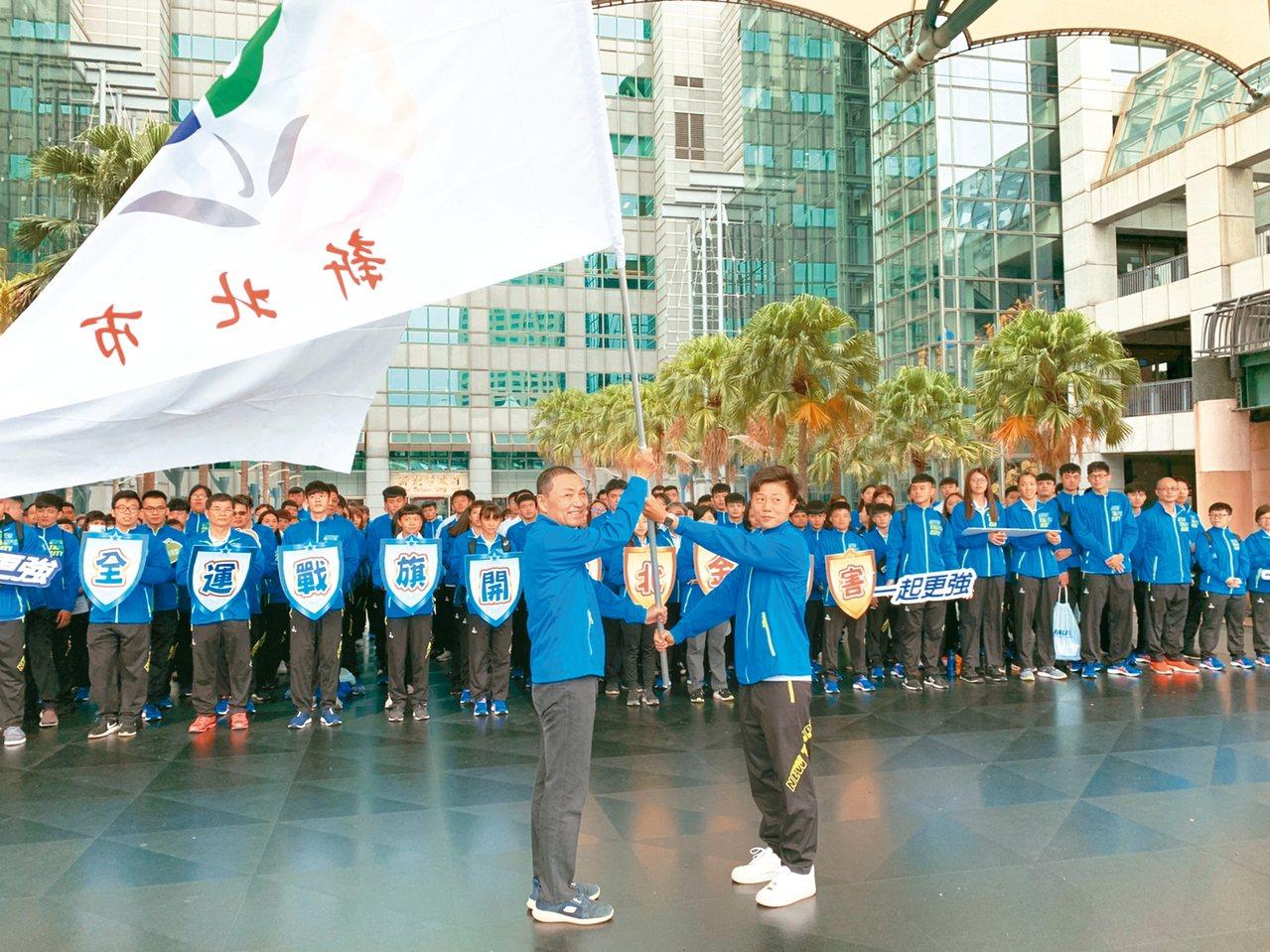 新北市長侯友宜(前左)昨為全運會選手打氣,授旗給進軍東奧的射箭選手雷千瑩(右)。...