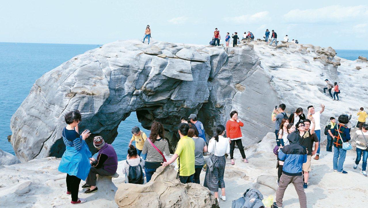 新北市瑞芳深澳「象鼻岩」假日吸引大批遊客,但當地長期無人管理,遊客涉險攀爬。 圖...